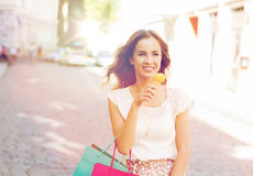 Woman with shopping bags and ice cream in city. Sale, consumerism, summer and people concept - happy young woman with shopping bags and ice cream on city street Stock Photos