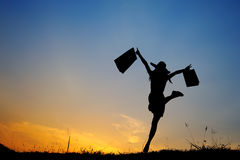 Woman and shopping bags jump in sunset silhouette Royalty Free Stock Photos