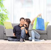 Woman with shopping bags kissing her boyfriend Stock Photo