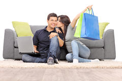 Woman with shopping bags kissing her boyfriend Royalty Free Stock Photography