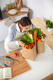 Woman with shopping bags in the kitchen at home, Stock Photo