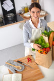 Woman with shopping bags in the kitchen at home, Royalty Free Stock Photos