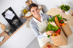 Woman with shopping bags in the kitchen at home, Stock Images