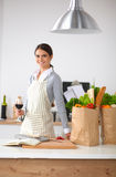 Woman with shopping bags in the kitchen at home, Royalty Free Stock Photo