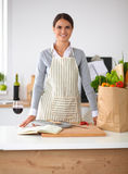 Woman with shopping bags in the kitchen at home, Royalty Free Stock Image