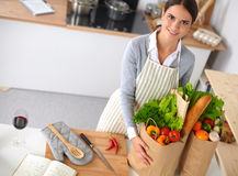 Woman with shopping bags in the kitchen at home, Royalty Free Stock Photography