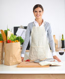 Woman with shopping bags in the kitchen at home, Royalty Free Stock Images