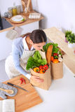 Woman with shopping bags in the kitchen at home Royalty Free Stock Images