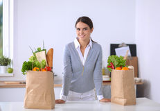 Woman with shopping bags in the kitchen at home Stock Photography