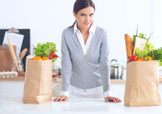 Woman with shopping bags in the kitchen at home, standing near desk Stock Photos