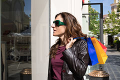 Woman with shopping bags looking at store showcase Royalty Free Stock Photos