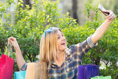Woman with shopping bags make selfie Stock Images