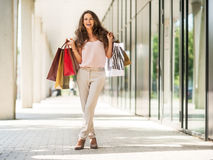 Woman with shopping bags on the mall alley. Full length portrait of happy young woman with shopping bags on the mall alley Stock Image