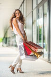 Woman with shopping bags on the mall alley. Full length portrait of smiling young woman with shopping bags on the mall alley Royalty Free Stock Photo