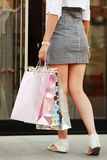 Woman with shopping bags at the mall doorway Royalty Free Stock Images