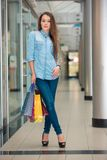 Woman with a shopping bags in the mall Stock Images