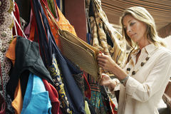 Woman Shopping For Bags On Market Stall Royalty Free Stock Photos