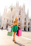 Woman with shopping bags in Milan. Young woman walking with colorful shopping bags on the main square in front of the famous duomo cathedral in Milan. Happy Stock Images