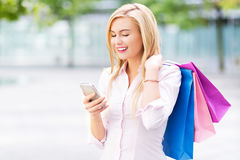 Woman with shopping bags and mobile phone Royalty Free Stock Photography