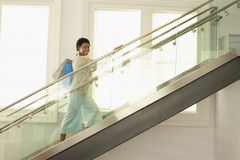 Woman With Shopping Bags On Modern Glass Stairs. Portrait of happy young woman walking up the modern stairs with shopping bags Stock Photos