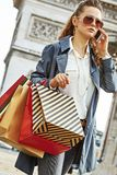 Woman with shopping bags near Arc de Triomphe using cell phone. Stylish autumn in Paris. trendy woman in trench coat  with shopping bags near Arc de Triomphe in Royalty Free Stock Photo