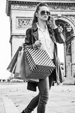 Woman with shopping bags near Arc de Triomphe using cell phone. Stylish autumn in Paris. trendy woman in trench coat  with shopping bags near Arc de Triomphe in Royalty Free Stock Image