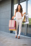 Woman with shopping bags near shop door Stock Photos