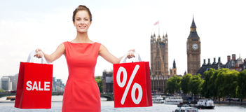 Woman with shopping bags over london city. Sale, discount, tourism and holidays concept - smiling young woman in red dress with shopping bags with percent sign Stock Images