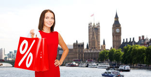 Woman with shopping bags over london city. Sale, discount, tourism and holidays concept - smiling young woman in red dress with shopping bags with percent sign Royalty Free Stock Photo