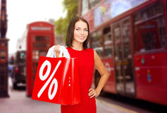 Woman with shopping bags over london city street. Sale, discount, tourism and holidays concept - smiling young woman in red dress with shopping bags with percent Stock Photo