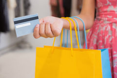 Woman with shopping bags paying by credit card Stock Images