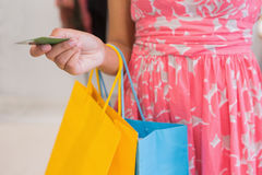 Woman with shopping bags paying by credit card Stock Image