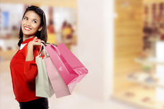 Woman With Shopping Bags. Portrait of young happy woman with shopping bags over blurred mall background stock images