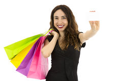 Woman with shopping bags presenting a blank sign card Royalty Free Stock Photo