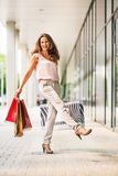 Woman with shopping bags rejoicing on mall alley Stock Images