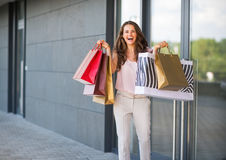 Woman with shopping bags rejoicing near shop door Royalty Free Stock Images