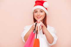 Woman with shopping bags in Santa Claus Stock Image