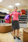 Woman with shopping bags at  shoe store. Happy mature woman with shopping bags at fashion shoe store Royalty Free Stock Photo