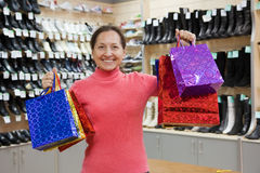 Woman with shopping bags at  shoes shop. Happy mature woman with shopping bags at  shoes shop Stock Photos