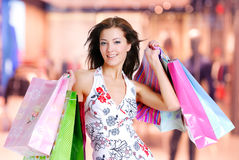 Woman with shopping bags at shop. Happy beautiful woman with shopping bags stands at shop stock photography