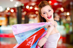 Woman with shopping bags at shop. Happy beautiful woman with shopping bags stands at shop royalty free stock photography