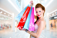 Woman with shopping bags at shop. Happy beautiful woman with shopping bags stands at shop royalty free stock image