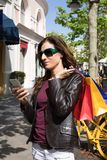 Woman with shopping bags on shoulder using mobile phone Stock Photography