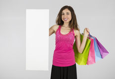 Woman with shopping bags showing blank banner Stock Photo