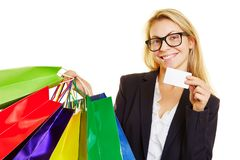 Woman with shopping bags shows credit card. Smiling woman with many colorful shopping bags shows credit card stock photography