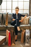 Woman with shopping bags sitting in apartment Stock Photo
