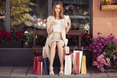 Woman with shopping bags sitting on bench. Royalty Free Stock Photo