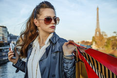 Woman with shopping bags and smartphone in Paris looking aside Royalty Free Stock Images