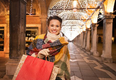 Woman with shopping bags standing under Christmas light, Venice Stock Photography