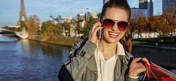 Woman with shopping bags talking on cell phone near Eiffel tower Stock Photo